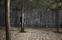 businessman standing behind tree in front of concrete wall