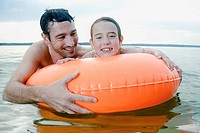 portrait of young girl and father swimming with floating tyre