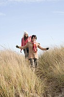 Female friends walking in marram grass
