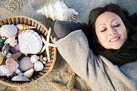 Woman lying on beach with shells