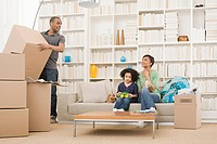 Man unpacking whilst woman and girl sit on sofa