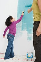 Girl and mother painting a wall