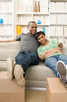 Couple on sofa with feet up on boxes