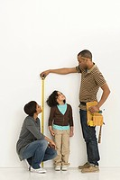 Parents measuring daughter