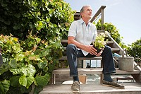 Man sitting on steps and holding plant
