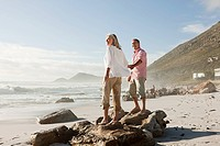 Couple standing on rocks on beach