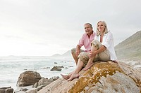 Couple sitting on rock by the sea