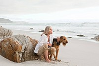 Mature woman and airedale terrier on a beach