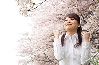 Businesswoman standing underneath cherry trees