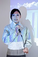 Businesswoman giving presentation with projector screen