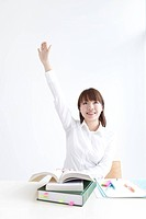 Young woman raises her hand while studying at her desk
