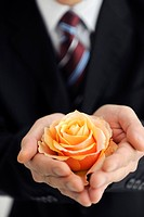 Businessman holding orange rose