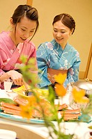 Women dressed in yukatas sitting down to eat a meal