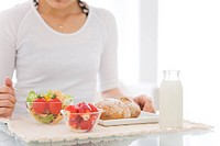 Woman eating meal of salad, strawberries and bread rolls