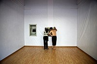 A man and a woman take money from an ATM austere. China