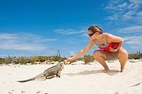 Woman feeding iguana, Exumas, Bahamas