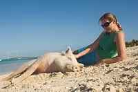 Woman with wild pig on Big Majors Cay, Exumas, Bahamas