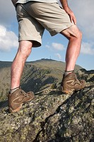 A hiker stretching leg on Mount Clay with Mount Washington in the background  Located in the White Mountains, New Hampshire USA Notes: Mount Washingto...