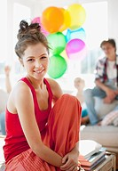 Woman smiling with friends holding balloons in background