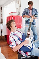 Men playing electric guitar and ukulele