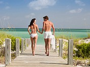 Couple in bathing suits holding hands and walking toward ocean