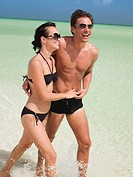 Couple in bathing suits wading in ocean