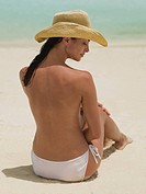 Woman in sun hat sitting on beach topless