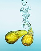 Pears splashing in water