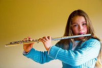 A young female music student playing the flute
