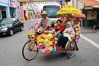 A Malay Muslim family riding in a colourfully decorated trishaw in Malacca