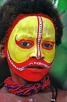 A Huli boy with traditional yellow and red painted face Tari, Southern Highlands, Papua New Guinea