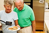 Senior mature couple ages 64 and 65 preparing blueberry pancakes together