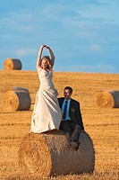 newly-wed couple in their wedding clothes in field of hay