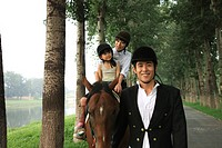 Girl with his parents riding horse