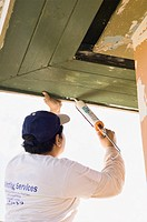 Latin man caulking roof eaves