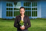 Mixed race woman holding flowers in pot