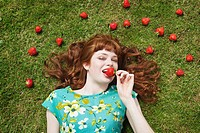 girl in grass surrounded by strawberries