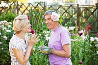 woman laughs at man with rose behind ear