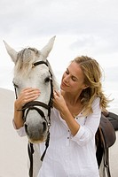 White horse, blond woman, sand, beach