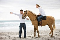 Brown horse, man, woman, beach, sea, sand