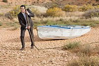 Businessman towing a boat in the desert