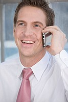 Germany, Munich, business man using mobile phone, smiling, portrait (thumbnail)