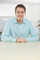 Germany, Munich, young man in office, arms crossed, smiling, portrait, close_up