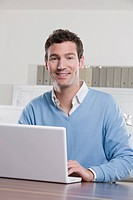 Germany, Munich, business man in office using laptop, smiling, portrait