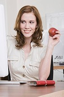 Germany, Munich, young woman in office having a snack