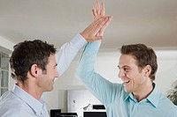 Germany, Munich, two businessmen in office giving high five, smiling, portrait