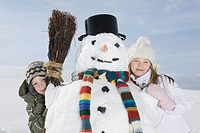 Germany, Bavaria, Munich, Boy 8_9 and girl 8_9 standing next to snowman, portrait