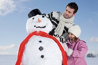 Germany, Bavaria, Munich, Father and daughter 6_7 making a snowman, portrait