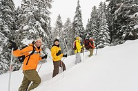 Italy, South Tyrol, People snowshoeing uphill