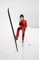 Italy, South Tyrol, Woman with skis, fooling about